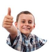Boy sitting at a desk with a laptop and giving a thumbs up