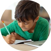 Boy using laptop while drawing a sketch on book at home