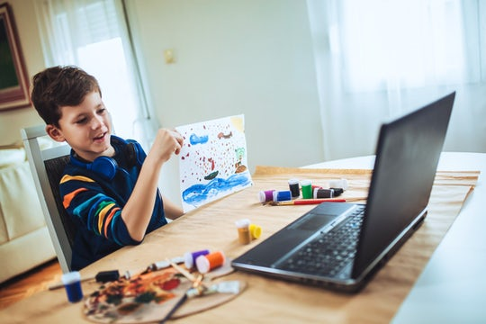 Focused boy painting and watching online course on laptop while practicing at home. Online training, online classes.