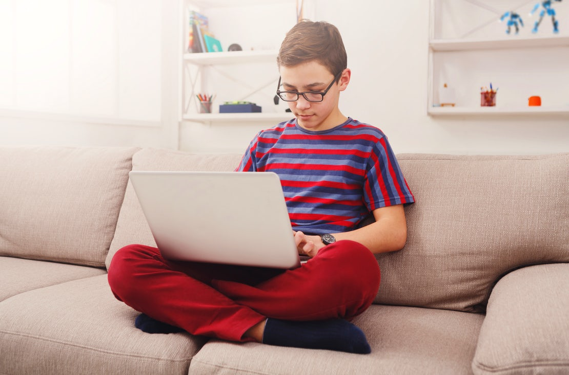 Teenage boy using laptop on couch at home